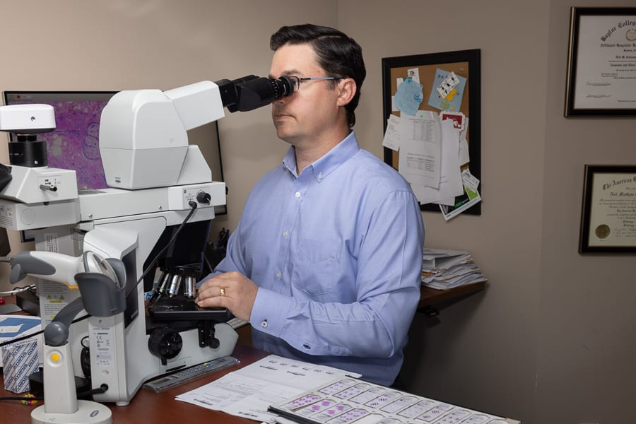 Neil Coleman looking through a microscope in his office
