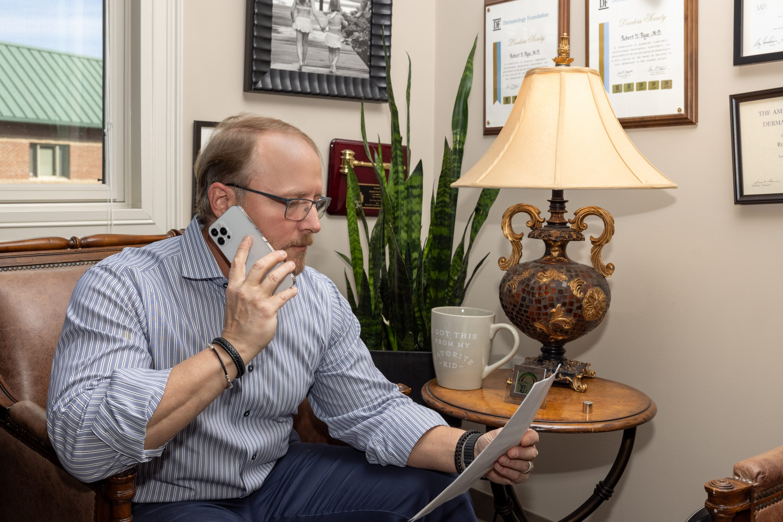 physician on a phone call and reading a document