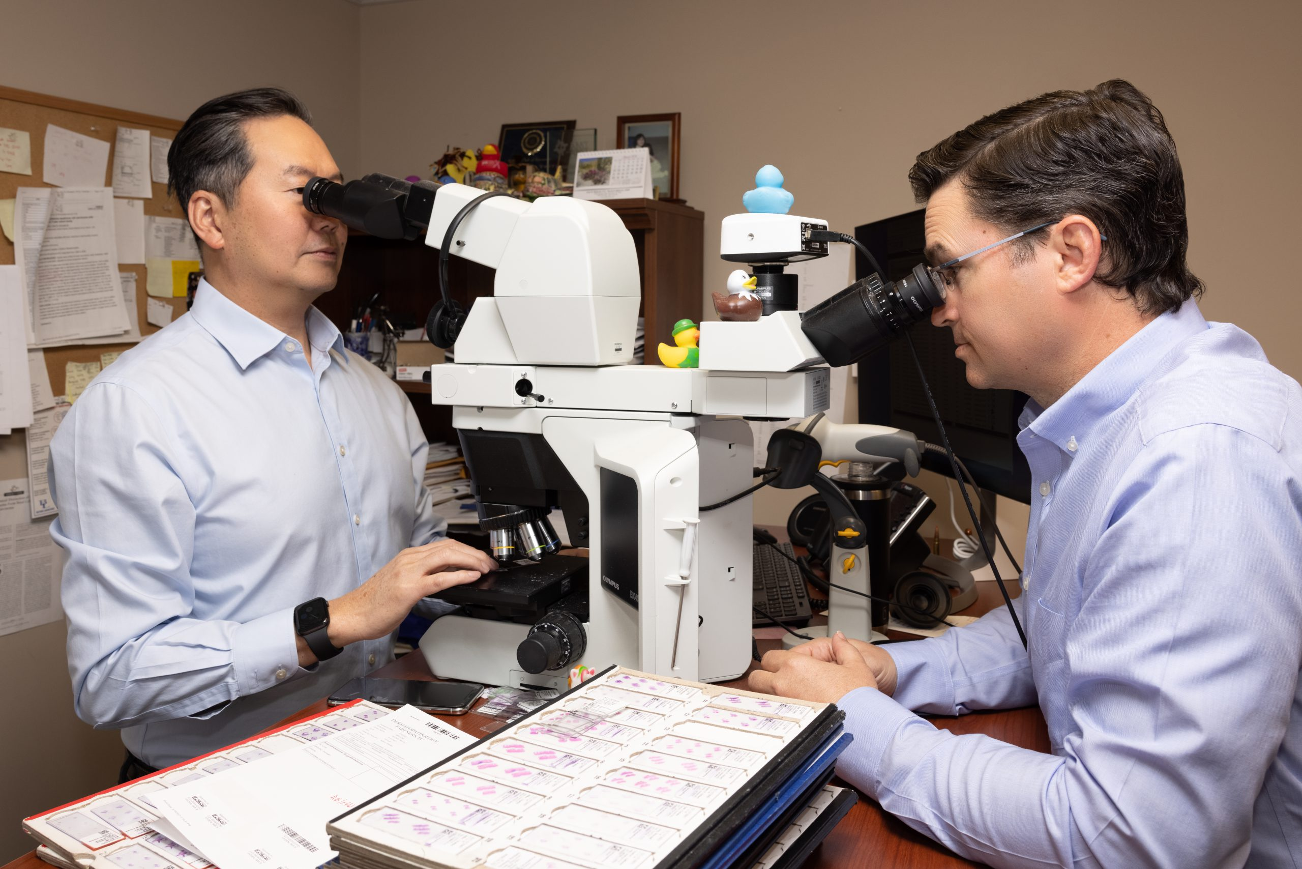 two pathologists looking at specimen through microscopes