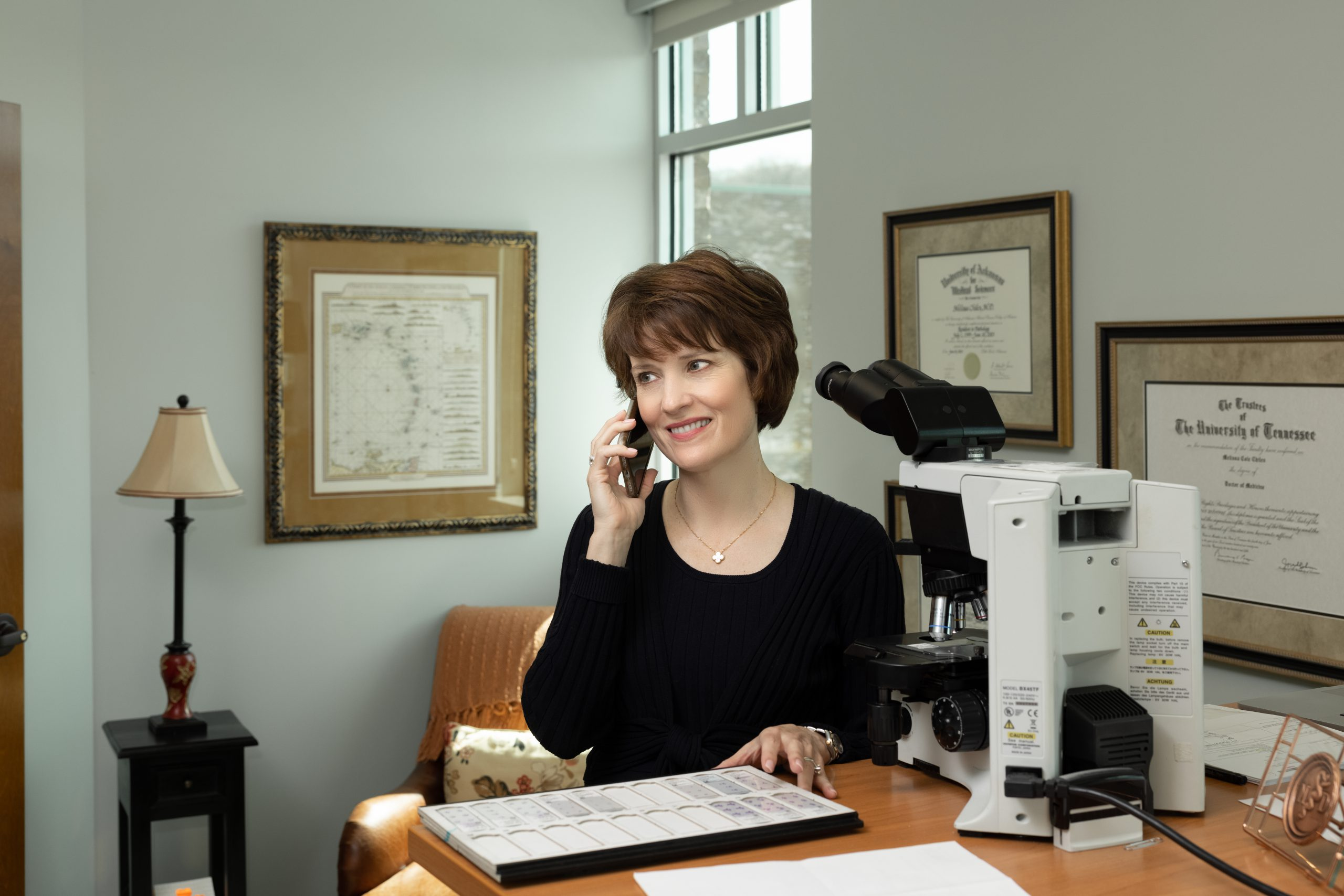 doctor on the phone at her desk with a microscope